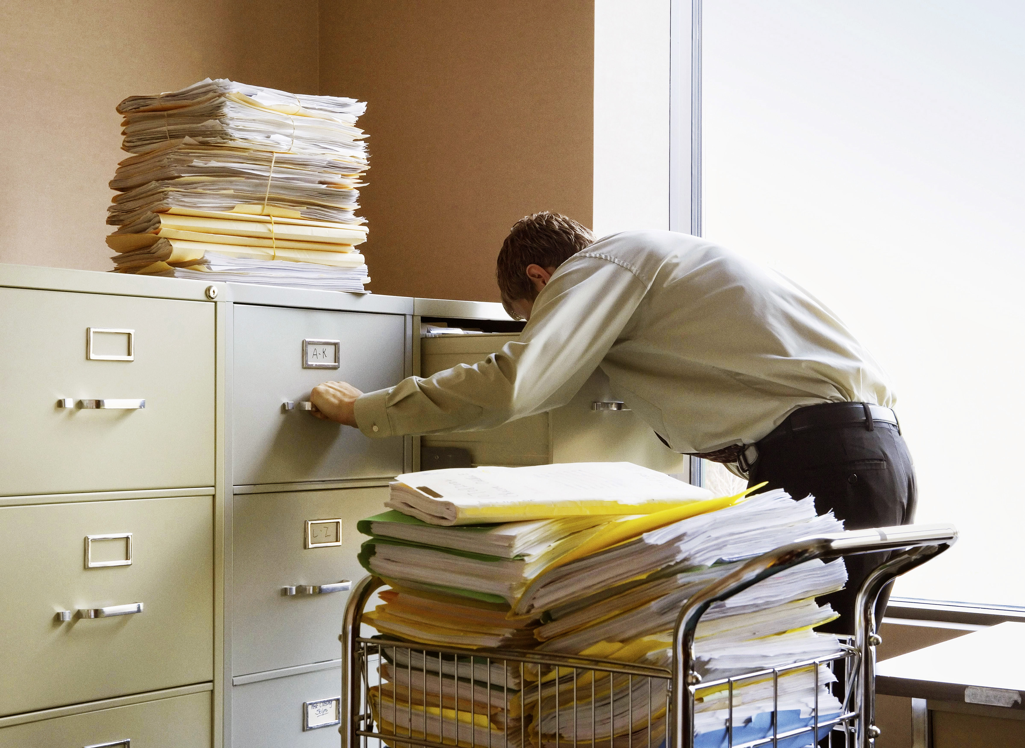 Businessman searching for documents in metal file cabinets.